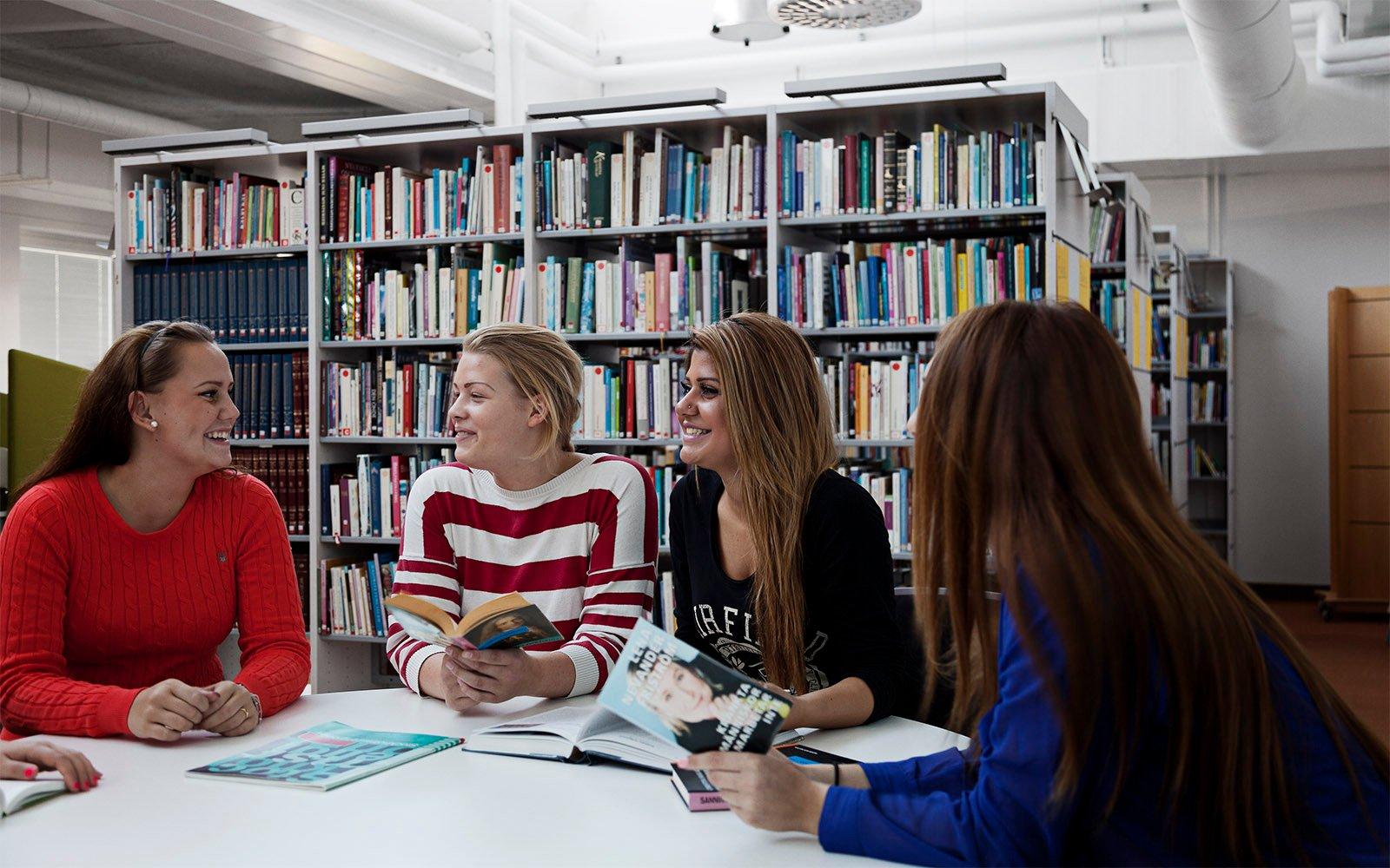 Studerende fra Sågbäcksgymnasiet siddende på skole biblioteket oplyst af naturligt sollys