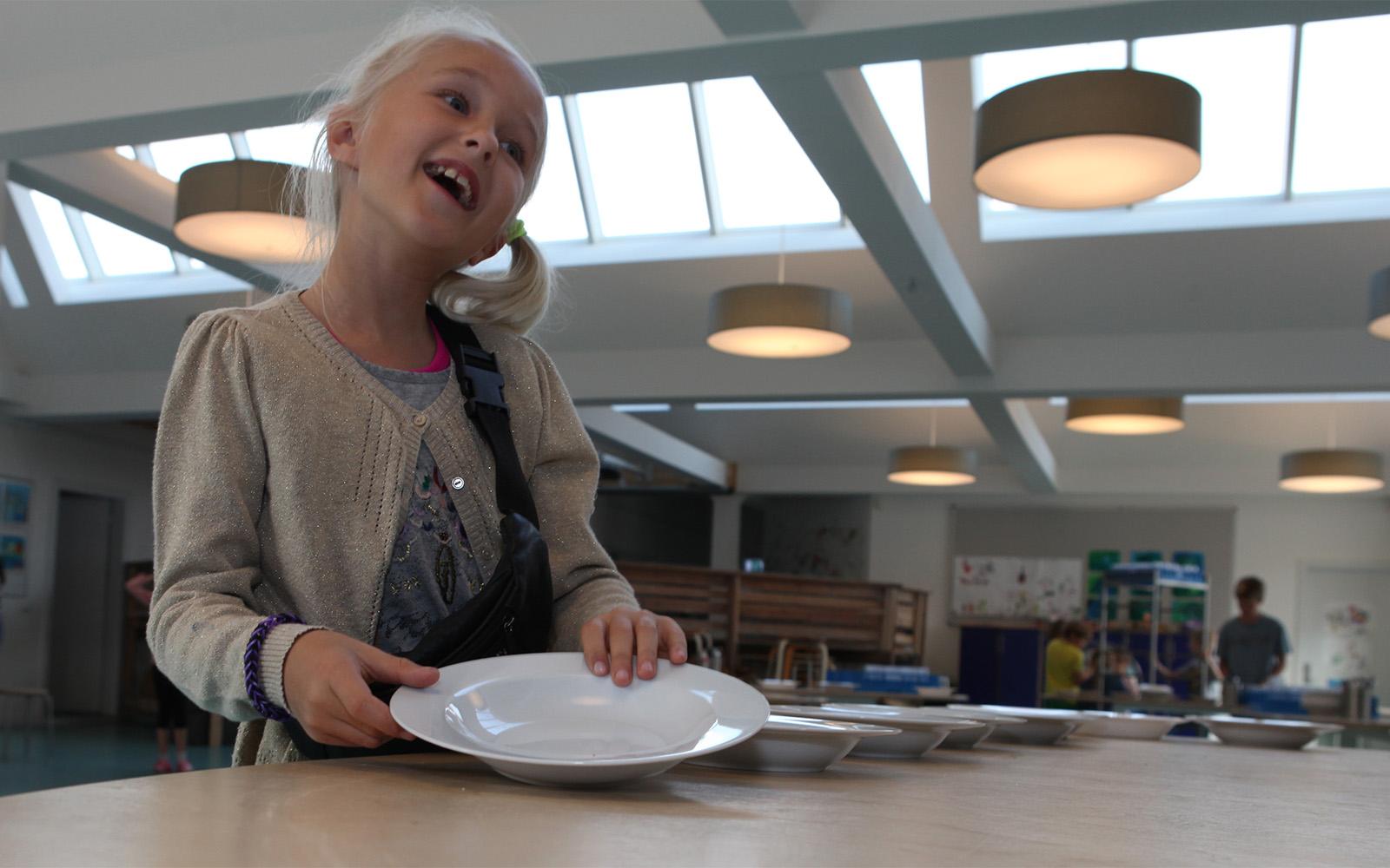 Ung studerende i cafeteriet oplyst af ovenlys og kunstig belysning