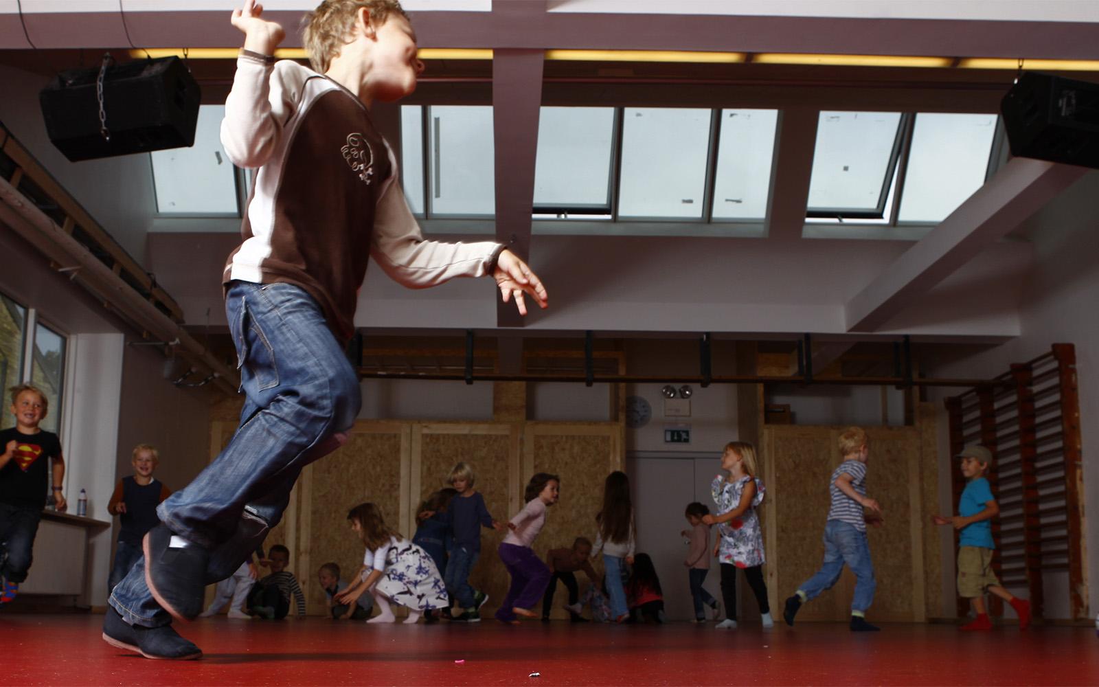 Børn leger i skolens gymnastiksal med ovenlys og tagventilation