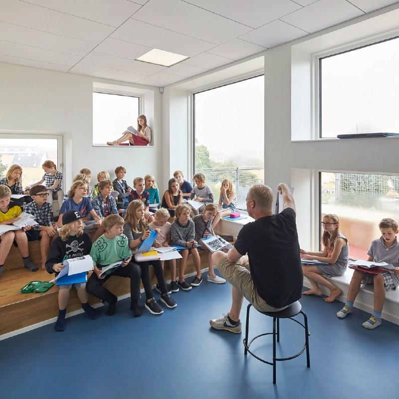 Klasseværelse fyldt med naturligt lys og moderne stole opstilling